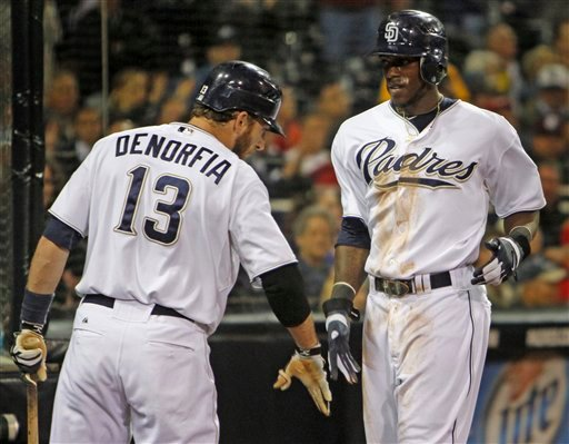 San Diego Padres' Cameron Maybin, right, lows fives with Chris Denorfia after scoring against the St. Louis Cardinals in the seventh inning of a baseball game Monday, May 23, 2011 in San Diego. (AP Photo/Lenny Ignelzi)