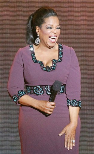 """In this May 17, 2011 photo,Oprah Winfrey acknowledges fans during a star-studded double-taping of """"Surprise Oprah! A Farewell Spectacular,"""" in Chicago."""