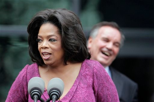 """Chicago Mayor Richard M. Daley laughs in the background as talk-show host Oprah Winfrey speaks to fans after a street outside Harpo Studios in Chicago was named """"Oprah Winfrey Way"""" in her honor Wednesday, May 11, 2011."""
