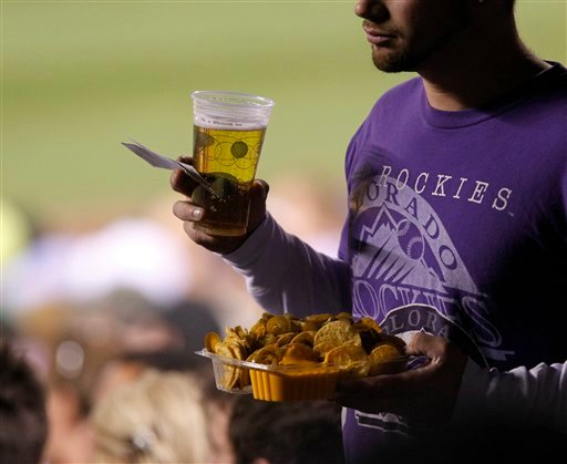In this photo taken May 9, 2011, a fan carries a beer and nachos on his way to his seat at a Colorado Rockies baseball game at Coors Field in Denver.