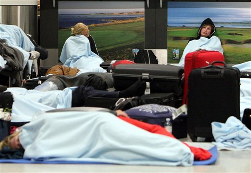 Passengers rest on the floor as their flights have been canceled at Edinburgh Airport in Edinburgh, Scotland Tuesday, May 24, 2011.