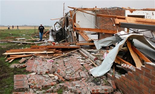 Matt McElvany walks past the home of his friend, Brent Boutwell, not in photo, in Piedmont, Okla., following a tornado Tuesday, May 24, 2011. (AP Photo/Sue Ogrocki)