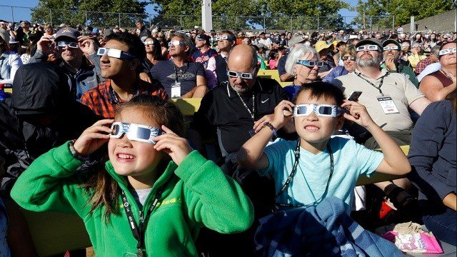 A crowd wears protective glasses as they watch the beginning of the solar eclipse from Salem, Ore., Monday, Aug. 21, 2017.
