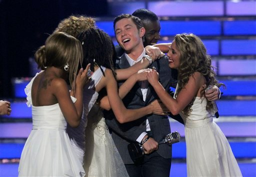 "Scotty McCreery reacts after winning at the ""American Idol"" finale on Wednesday, May 25, 2011, in Los Angeles. Other ""American Idol"" contestants are seen congratulating him. (AP Photo/Chris Pizzello)"