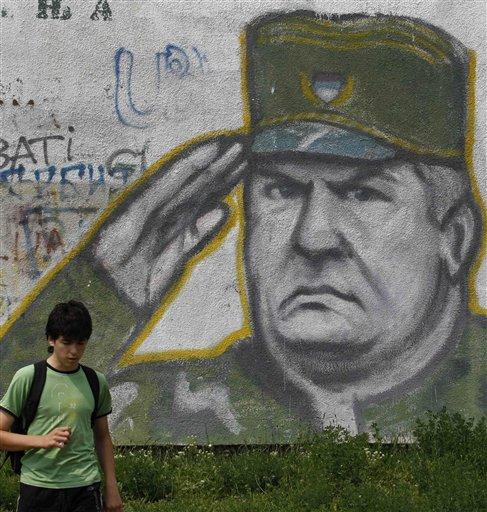 A boy walks pass graffiti of war crimes fugitive Bosnian Serb army commander Ratko Mladic in Belgrade, Serbia, Thursday, May 26, 2011. Serbia's President Boris Tadic confirms war crimes fugitive Ratko Mladic has been arrested. (AP Photo/Andrej Cukic)