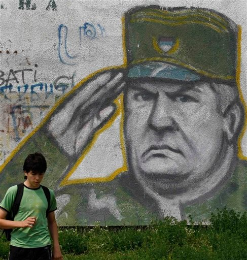A boy walks pass graffiti of war crimes fugitive Bosnian Serb army commander Ratko Mladic in Belgrade, Serbia, Thursday, May 26, 2011. Serbia's President Boris Tadic confirms war crimes fugitive Ratko Mladic has been arrested. (AP Photo/Andrej Cukic)