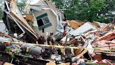 Monroe County Sheriff's officers Allen Mullis, left, and Jeff Branham examine the damage from a severe storm that damaged a trailer park, Thursday, May 26, 2011, in Bloomington, Ind. (AP Photo/Darron Cummings)