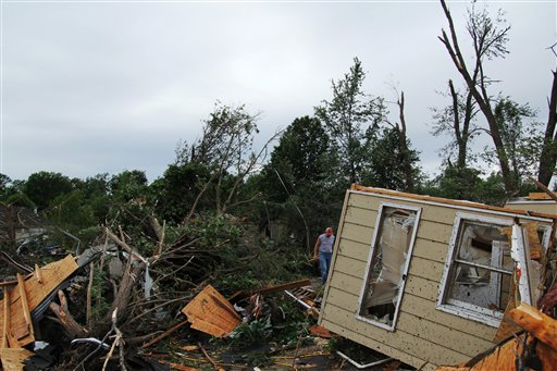A man makes his way through the wreckage of a home damaged by a tornado in Sedalia, Mo., on Wednesday, May 25, 2011. (AP Photo/Dan Gill)