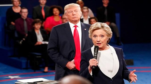 Democratic presidential nominee Hillary Clinton, right, speaks as Republican presidential nominee Donald Trump listens.