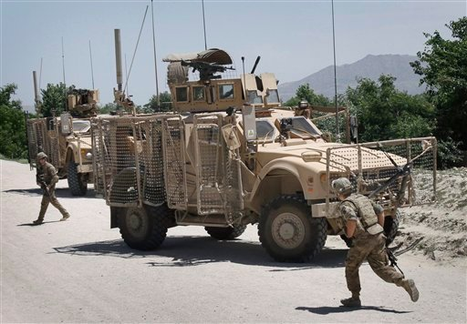 U.S. soldiers with the NATO led International Security Assistance Force react after their convoy was attacked by a suicide attacker using a motorcycle in Qarghayi, Laghman province east of Kabul, Afghanistan May 9, 2011. (AP Photo/Rahmat Gul)
