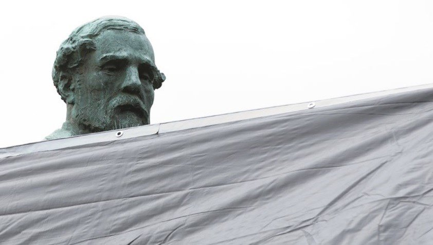 Workers in Charlottesville draped giant black covers over two statues of Confederate generals on Wednesday to symbolize the city's mourning for a woman killed while protesting a white nationalist rally.
