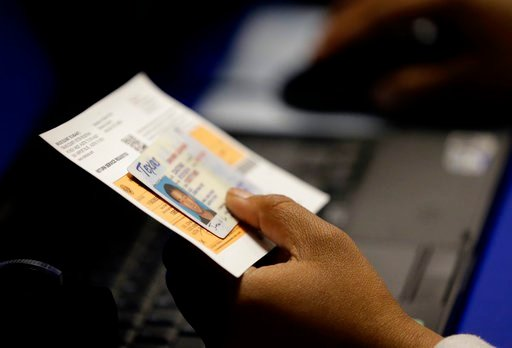 FILE - In this Feb. 26, 2014, file photo, an election official checks a voter's photo identification at an early voting polling site in Austin, Texas. A judge has ruled for a second time that Texas' strict voter ID law was intentionally crafted to discrim