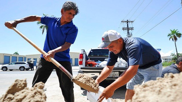 Leo Sermiento, left, and Emilio Gutierrez, right, fill sandbags in preparation of a tropical system on Wednesday, Aug. 23, 2017, on South Padre Island, Texas.