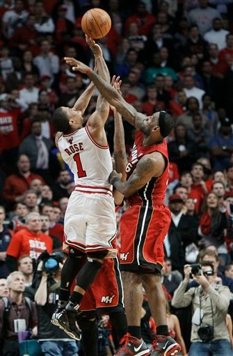 Chicago Bulls guard Derrick Rose (1) shoots against Miami Heat forwards Udonis Haslem, rear, and LeBron James, right, at the end of Game 5 of the NBA basketball Eastern Conference finals.