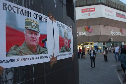 Posters with photos of war crimes suspect Ratko Mladic with text on cyrillic letter 'Rise up, Serb!' and 'the wing is broken but the flight will be remembered' are plastered on a wall downtown Banja Luka, 240 kms northwest of Sarajevo, Bosnia, on Friday,
