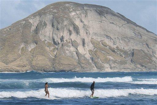 This Friday, Jan. 5, 2007 file photo shows surfers riding the waves at Waimanalo, Hawaii. Waimanalo.