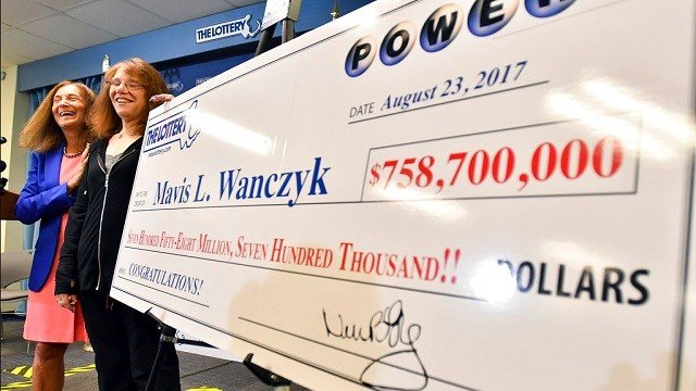 Mavis Wanczyk, of Chicopee, Mass., stands by a poster of her winnings during a news conference where she claimed the $758.7 million Powerball prize.