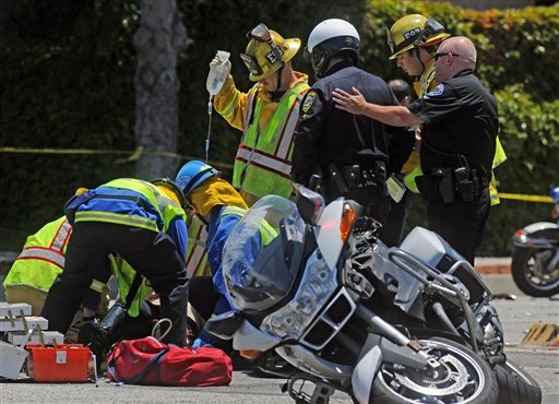 Emergency crews work on an El Segundo police officer injured in a traffic accident which included another motorcycle officer from the Hawthorne Police Department on Hawthorne Boulevard, Thursday, May 26, 2011 in Torrance, Calif.