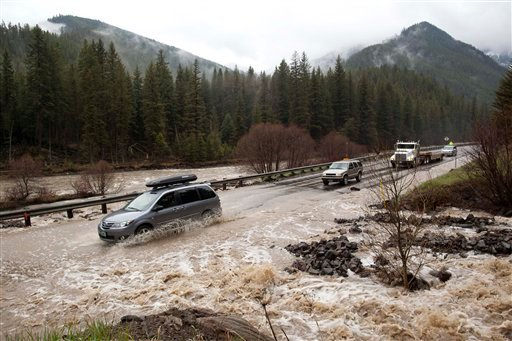 Motorists make their way southbound on U.S. Highway 191 across a tributary overflowing into the Gallatin River, Saturday, May 21, 2011, north of Big Sky, Mont.