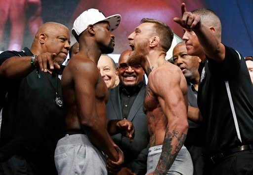 Floyd Mayweather Jr., center left, and Conor McGregor face off during a weigh-in Friday, Aug. 25, 2017, in Las Vegas. The two are scheduled to fight in a boxing match Saturday in Las Vegas. (AP Photo/John Locher)