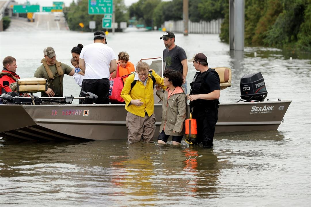 Residents are helped from a boat after being rescued from their flooded homes from Tropical Storm Harvey, Sunday, Aug. 27, 2017, in Houston. (AP Photo/David J. Phillip)