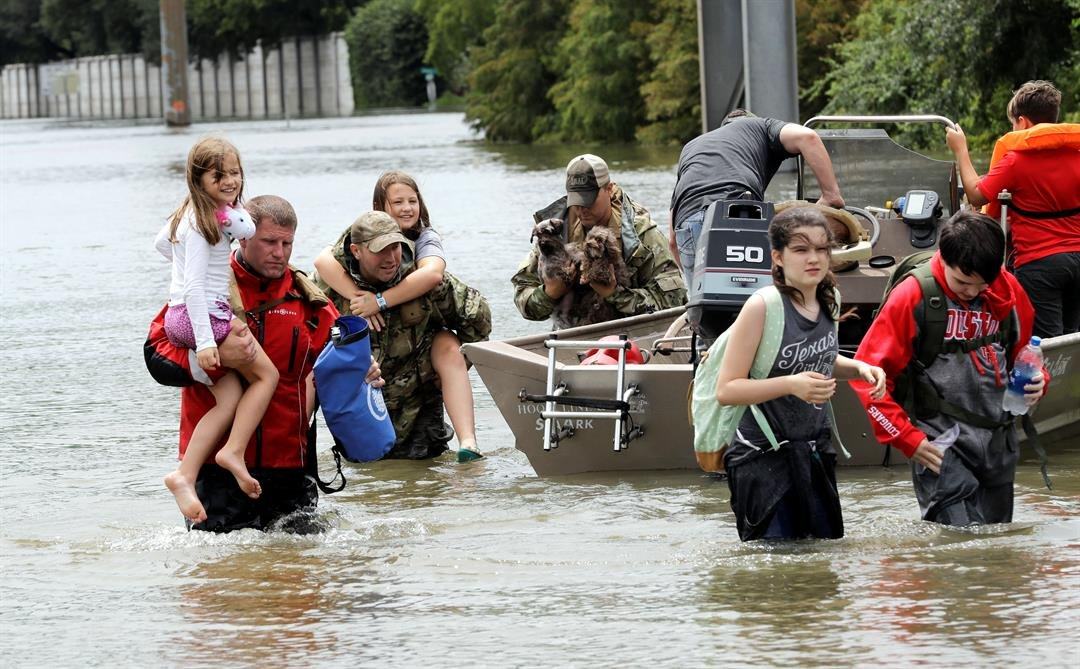 Residents are rescued from their homes surrounded by floodwaters from Tropical Storm Harvey Sunday, Aug. 27, 2017, in Houston, Texas. (AP Photo/David J. Phillip)
