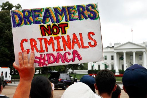 FILE- In this Aug. 15, 2017, file photo, a woman holds up a signs in support of the Obama administration program known as Deferred Action for Childhood Arrivals, or DACA. (AP Photo/Jacquelyn Martin, File)