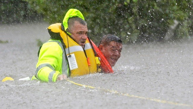 Wilford Martinez, right, is rescued from his flooded car by Harris County Sheriff's Department Richard Wagner along Interstate 610.