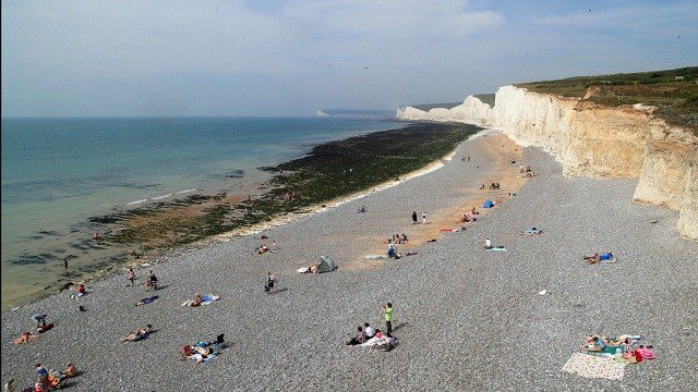 People relax on the beach at Birling Gap in Eastboune, Sussex, England, on Monday, Aug. 28, 2017.