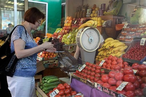 A customer buys vegetables and fruits at a street side market in Moscow, Russia, on Tuesday, May 31, 2011.