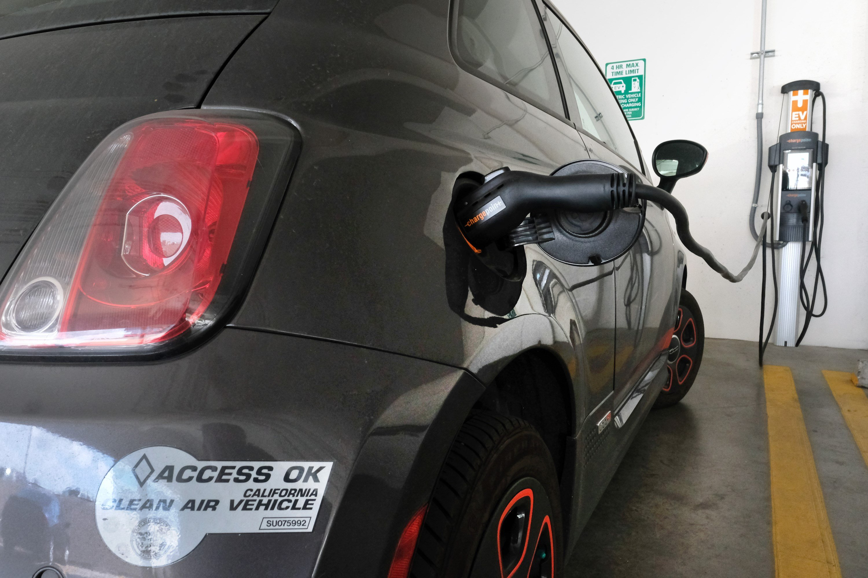 FILE - This April 25, 2016 file photo photo shows an electric Fiat plugged into a charging station in a parking lot in Los Angeles. (AP Photo/Richard Vogel,File)