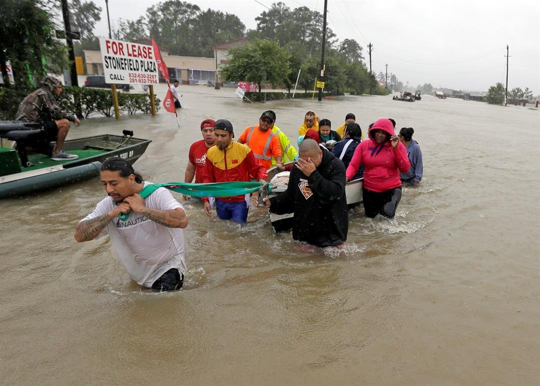 Evacuees wade down Tidwell Road as floodwaters from Tropical Storm Harvey rise Monday, Aug. 28, 2017, in Houston. (AP Photo/David J. Phillip)