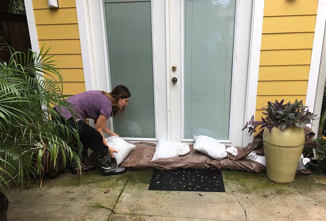 Nancy Gunn adjusts sandbags at a doorway into the Auld Sweet Olive Bed and Breakfast in New Orleans on Tuesday, Aug. 29, 2017.  (AP Photo/Kevin McGill)