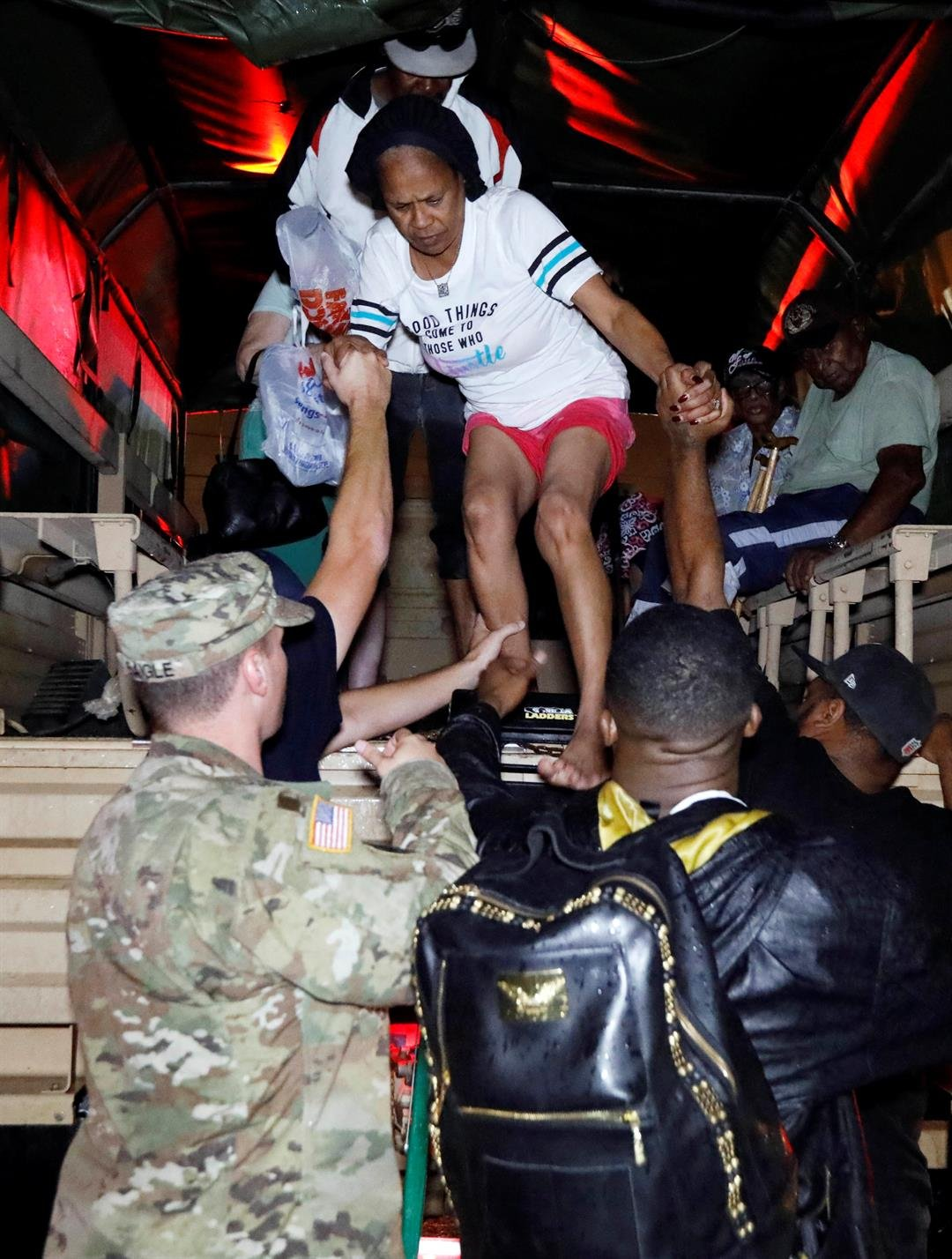 Lake Charles rescue personnel help residents exit from the back of a vehicle late Monday night, Aug. 28, 2017, in Lake Charles, La. (AP Photo/Rogelio V. Solis)