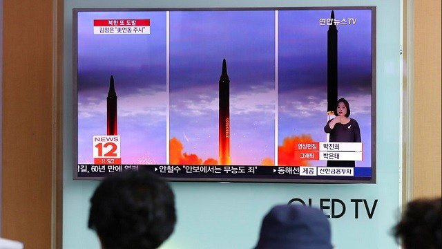 People watch a TV screen showing a local news program reporting about North Korea's missile launch.