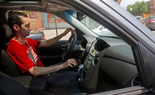 In this May 27, 2011 photo, Brad Levin drives his new Honda Pilot in New York. Rising prices prompted Levin of Stamford, Conn., to go ahead and buy a 2011 Honda Pilot in May.