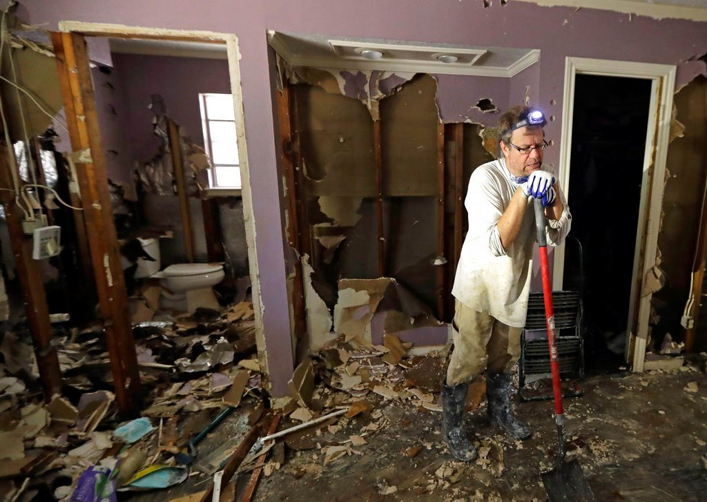 Edward Woods takes a break from cleaning up his mother's home, which was destroyed by floodwaters in the aftermath of Hurricane Harvey, Sunday, Sept. 3, 2017, in Spring, Texas. (AP Photo/David J. Phillip)