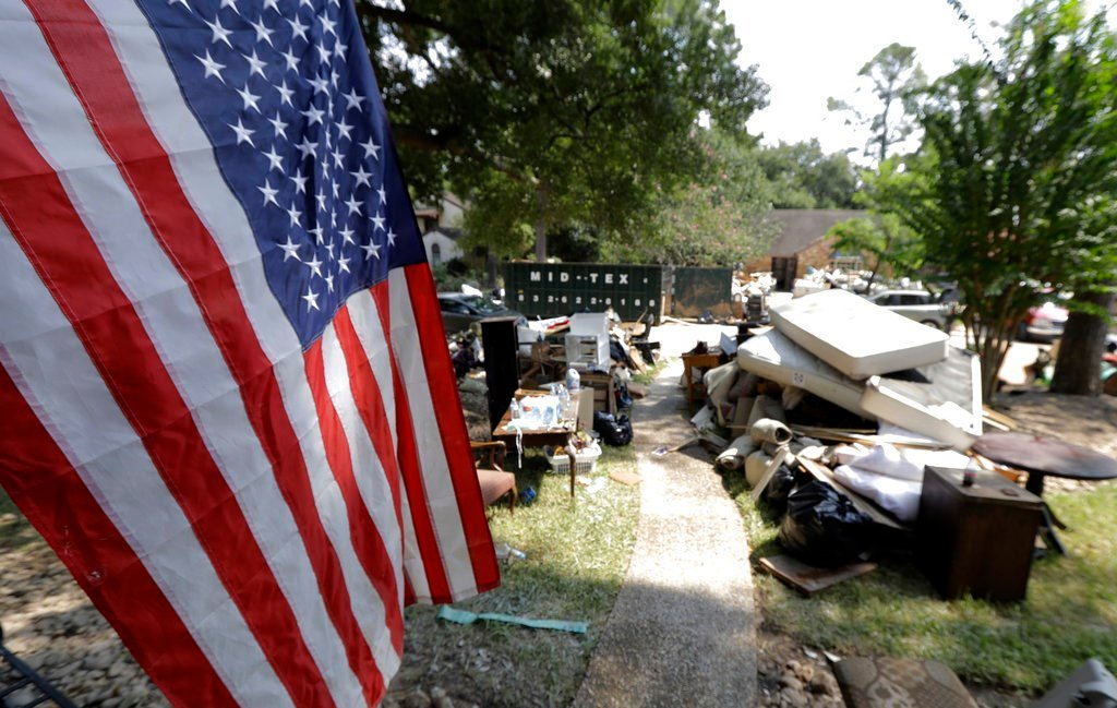 An American flag hangs outside a home damaged by floodwaters in the aftermath of Hurricane Harvey Sunday, Sept. 3, 2017, in Spring, Texas. (AP Photo/David J. Phillip)