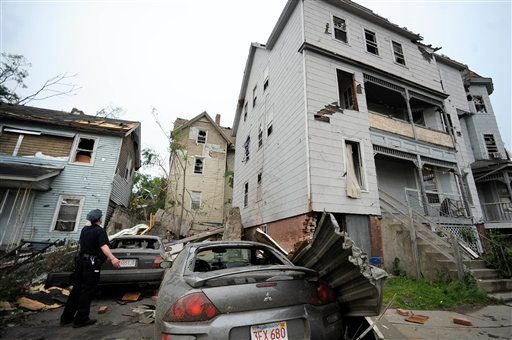 A police officer checks on people in a house after a reported tornado struck Springfield, Mass., Wednesday, June 1, 2011. (AP Photo/Jessica Hill)