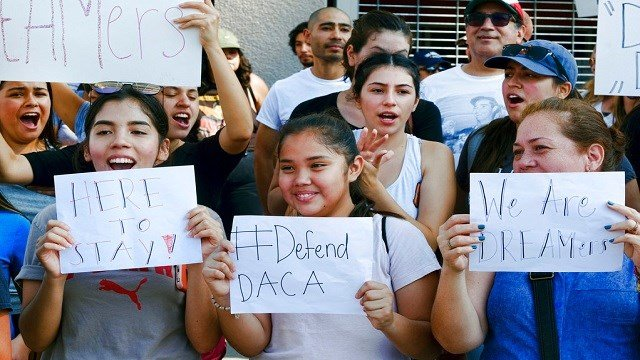 Supporters of the Deferred Action for Childhood Arrivals, or DACA, chant slogans and holds signs while joining a Labor Day rally in downtown Los Angeles.