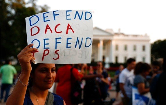 "A woman holds up a sign that reads ""Defend DACA Defend TPS"" during a rally supporting Deferred Action for Childhood Arrivals, or DACA, outside the White House."