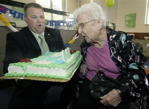 June Gregg, right, of Bainbridge, Ohio, blows out the candles on her birthday cake held by Doug Shoemaker, community president and branch general manager of the Chillicothe branch of Huntington National Bank, to celebrate Gregg's 100th birthday.