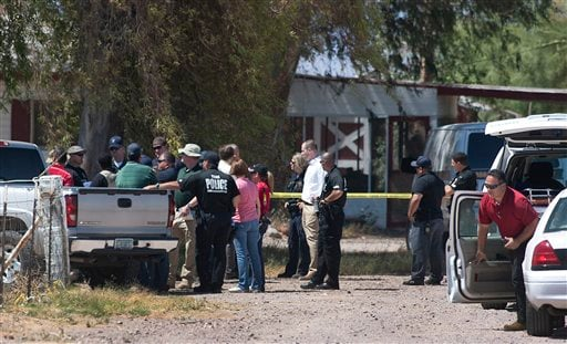 Police investigators comb over a farm property near Wellton, Arizona, Thursday, June 2, 2011.