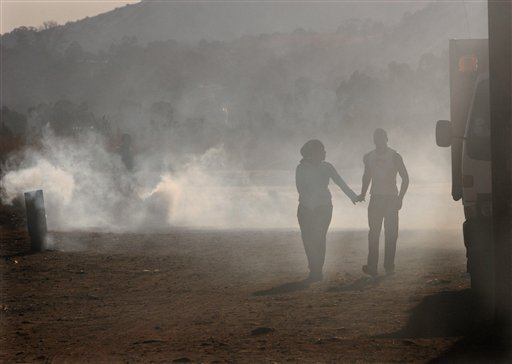 FILE In this Thursday, May 25, 2006 file photo, an unidentified couple walk hand-in-hand in the smoke-filled, poverty stricken, Tudor Shaft informal settlement, west of Johannesburg.