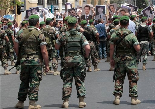 Lebanese army soldiers block the road in front of pro-Syrian regime protesters who they carry portraits of Syrian President Bashar Assad after they arrive near the mosque where supporters of an Islamic group, protest against the Syrian regime. (AP)