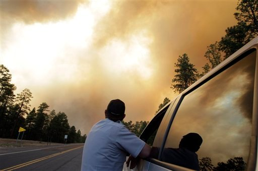 Navajo County Sheriff's Deputy, who declined to give his name, looks at smoke plumes from the Wallow fire as he talks to a truck driver in the Apache-Sitgreaves National Forest near Luna, N.M., Monday, June 6, 2011.
