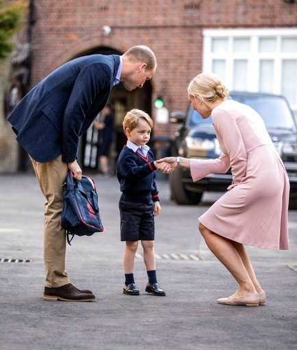 Britain's Prince William accompanies Prince George as he is greeted by Helen Haslem - the head of the lower school as he arrives for his first day of school at Thomas's school in Battersea, London.