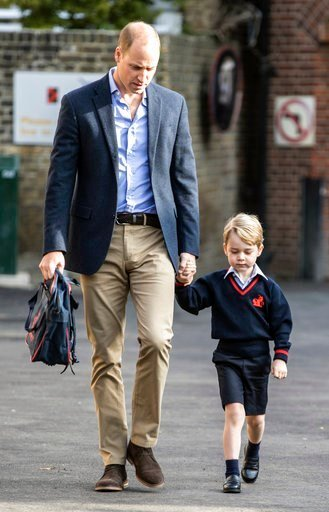 Britain's Prince William, left, holds Prince George's hand as he arrives for his first day of school at Thomas's school in Battersea, London, Thursday, Sept. 7, 2017.