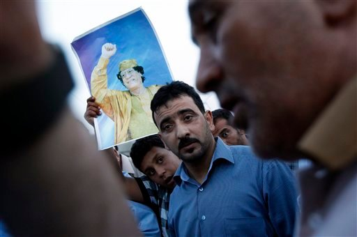 In this photo taken on a government organized tour, a boy holds a portrait of Libyan leader Moammar Gadhafi as local residents gather next to a damaged house in Tripoli, Libya. (AP)