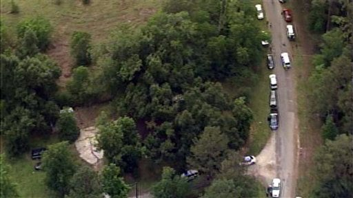 This image provided by KPRC-TV shows authorities at a rural house after receiving a tip that multiple dismembered bodies are buried there, in Liberty County, Texas, Tuesday, June 7, 2011. (AP Photo/KPRC-TV)